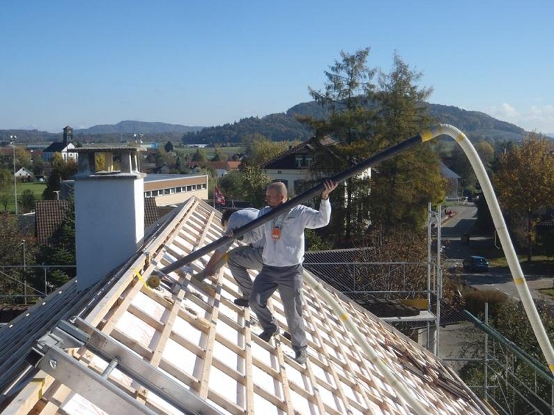 Dwóch mężczyzn na dachu docieplanie granulatem